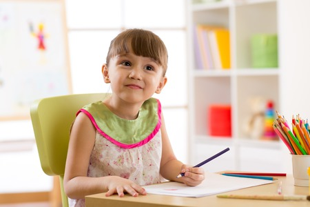Smiling kid drawing with color pencils in day care center Stock Photo
