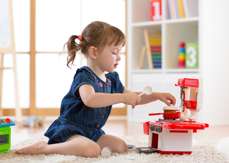 Pretty kid girl playing with a toy kitchen in children room Foto de archivo