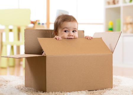 pretty baby infant boy sitting inside a box