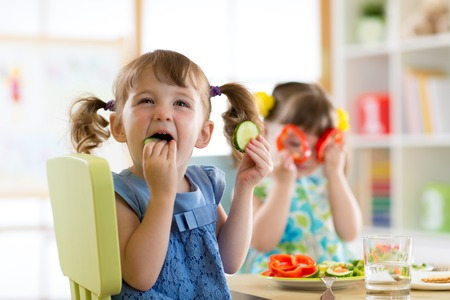 children kids eating vegetables in kindergarten or at home Stock Photo