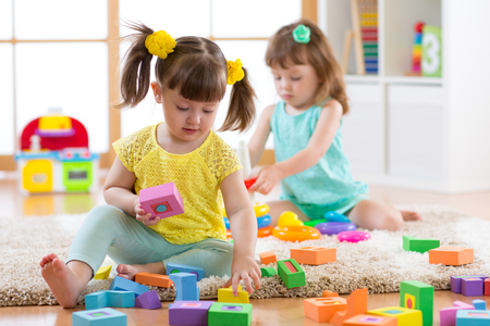 Kids playing with colorful block toys. Two children building towers at home or daycare centre. Educational child toys for preschool and kindergarten.
