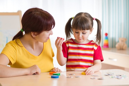 Kid playing with speech therapist
