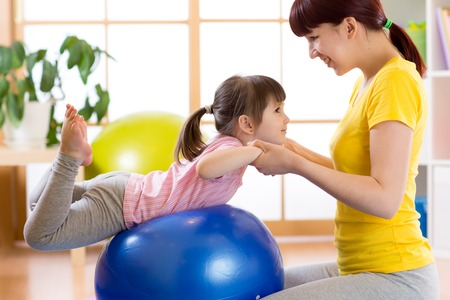 child girl doing gymnastic on fitness ball with mother at home