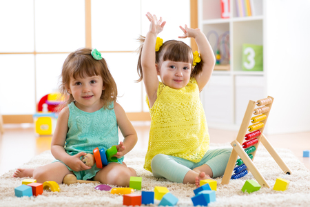 Little kids play with abacus and constructor toys, early learning