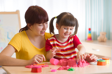 children at play: A cute little little girl and her mom playing with kinetic sand at home