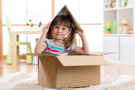 kid girl playing in a toy house in children room