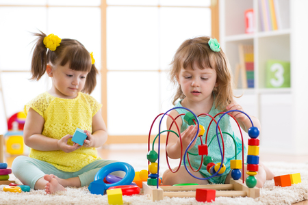 diligent: Children playing with toys in kindergarten Stock Photo