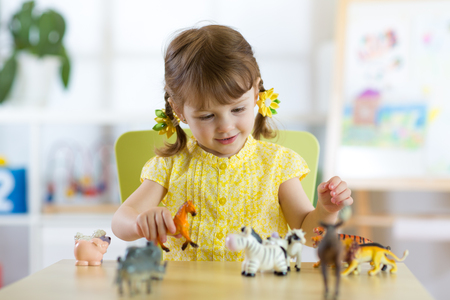 Happy little girl. Smiling child toddler plays animal toys at home or kindergarten. Stock Photo