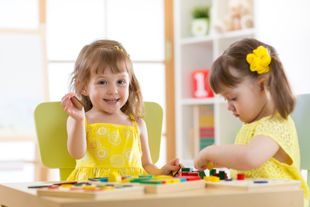 Kids playing block toys in playroom at nursery Stock Photo