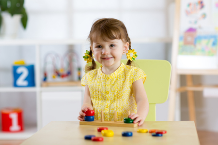 Kid girl playing with logical toy on desk in nursery room or kindergarten. Child arranging and sorting colors and sizes Stock Photo