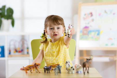 Kind spelen met dieren speelgoed aan tafel Stockfoto