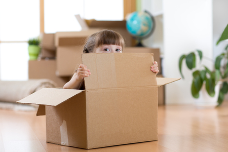 pretty child sitting inside a box after moving to new apartment