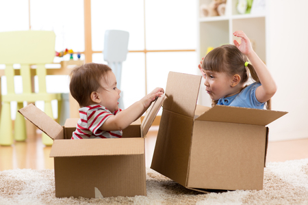 Kids in their new home having fun with cardboard boxes