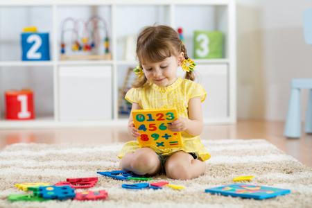 작은 소녀 자식 다채로운 플라스틱 숫자 또는 실내 숫자를 많이 놀고.