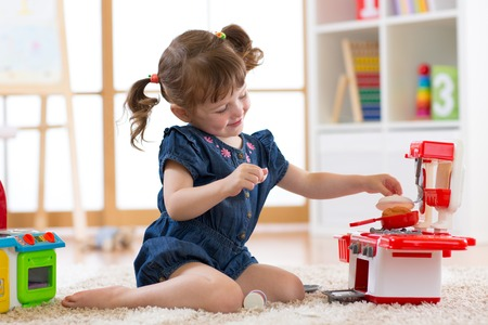 Little cute girl playing with utensil toys. Toddler kid in a playroom. Kid sitting on floor and cook in toy kitchen. Banque d'images