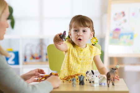 Happy little kid girl. Smiling child toddler plays animal toys at home or kindergarten Stock Photo