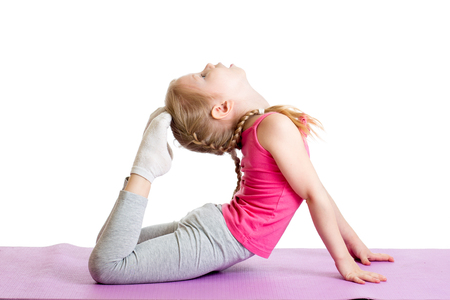Kid doing fitness exercises on mat. Isolated on white. photo
