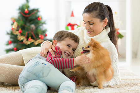 smiling family and dog sitting by Christmas tree Stock Photo