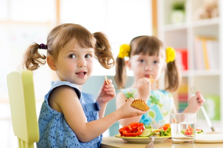 Children eating from plates in day care centre Stock Photo