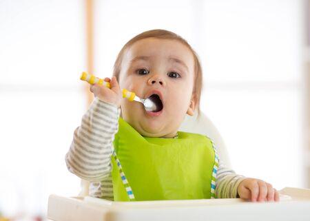smeared baby: Happy baby boy spoon eats itself Stock Photo