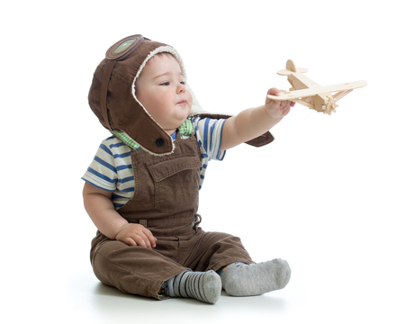 child boy playing with wooden plane isolated on white Stock Photo
