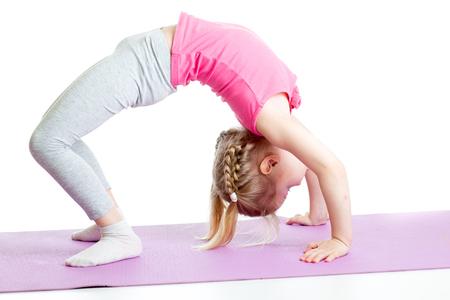 kid girl doing gymnastics on fitness mat photo