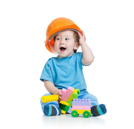 Toddler kid in hardhat plays with toy blocks over white background photo