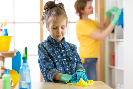 Kid girl and mother make cleaning in room at home Standard-Bild