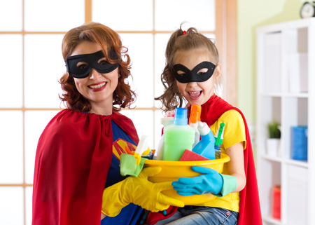 Mother and her child in Superhero costume. Mom and kid ready to house cleaning. Houseworking and housekeeping. photo