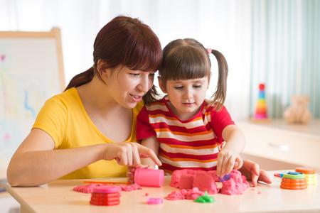 砂のおもちゃで遊んでのセラピストとの子。心理学者の作品、砂療法。