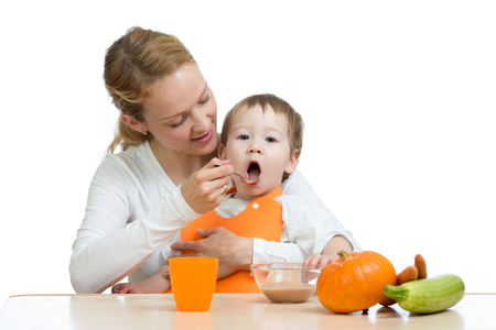 Mom feeding her kid with a spoon. Mother giving food to her little child. Healthy baby food and nutrition. photo