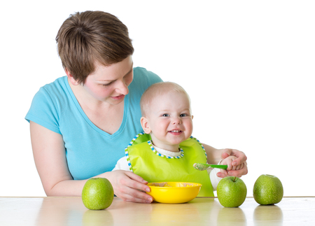 mother feeding kid boy with spoon isolated on white photo