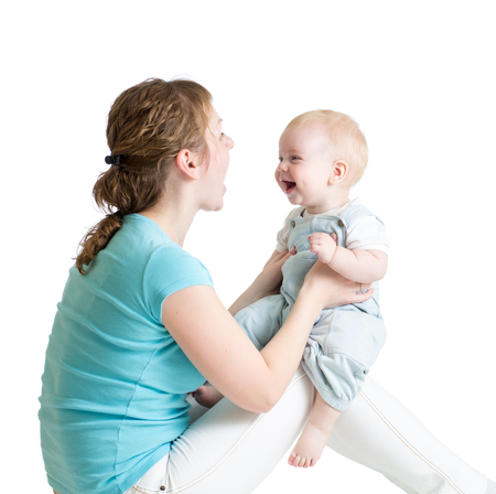 Charming baby boy looking at mommy and smiling while sitting on his mothers knees. Mom is looking at her child photo