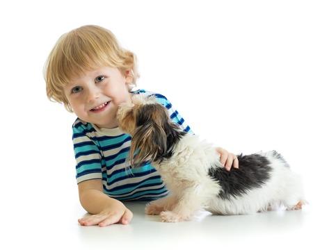 Kind kleine jongen met zijn puppy hond. Geïsoleerd op een witte achtergrond.
