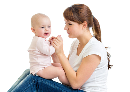 Charming baby girl looking away and smiling while sitting on his mothers knees. Mom is looking at her child