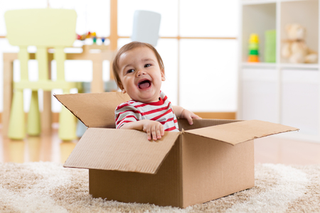예쁜 아기 유아 소년 상자 안에 앉아