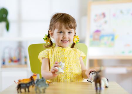 Bonne fille enfantine. Enfant enfant souriant joue des jouets pour animaux à domicile, préscolaire ou maternelle