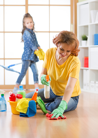 Happy family cleans the room. Mother and her daughter do the cleaning in the house. Stock Photo