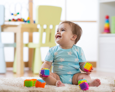 baby boy playing with toys at home nursery or kindergarten Stock Photo