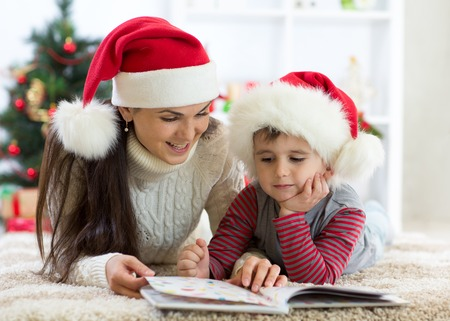 Child boy and his mother reading book at Christmas Stock Photo