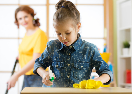 Une famille heureuse nettoie la pièce. Mère et fille de son fils font le ménage dans la maison. Une femme et une petite fille ont essuyé la poussière et ont aspiré le sol.