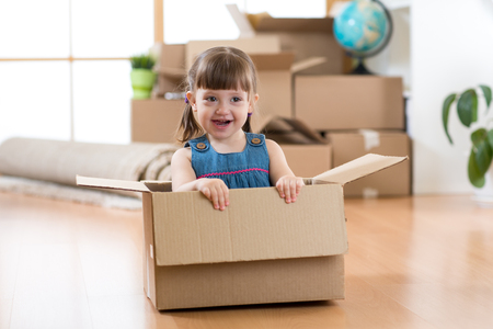 Just moved into a new home. Kid girl sits inside box. Stock Photo