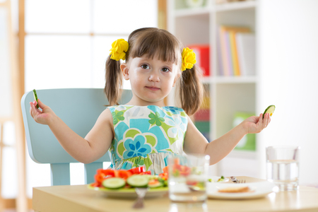 kid girl eating healthy vegetables in nursery