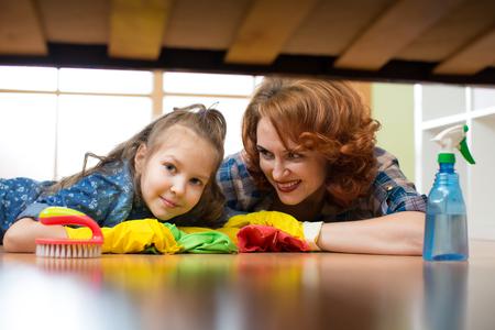 Mère et fille font le nettoyage dans la maison. Une femme heureuse et une petite fille ont essuyé le sol.