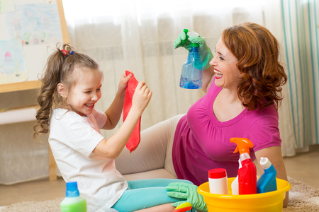 Happy family - woman and her cute little daughter are having fun, using a sprayer and a rag while cleaning their house Stock Photo