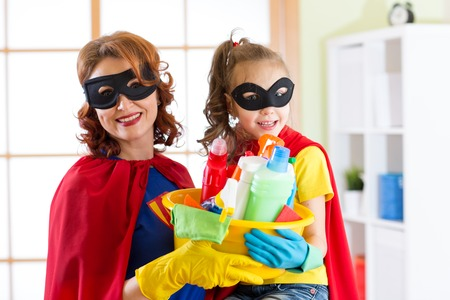 Mother and her child in Superhero costumes. Mom and kid ready to house cleaning. Housework and housekeeping. Stock Photo