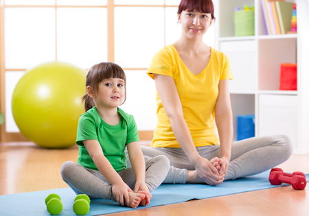 Mother and child daughter doing fitness exercises on mat at home