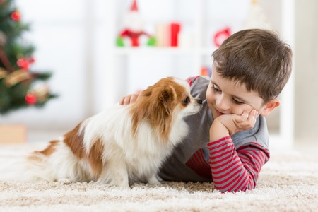 Little baby boy with dog lying on the floor Stock Photo