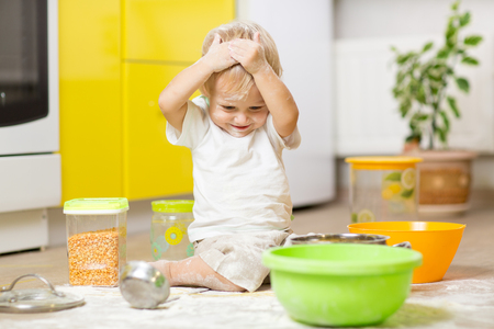 Playful child toddler with face soiled flour. Little boy surrounded kitchenware and foodstuffs Stock Photo