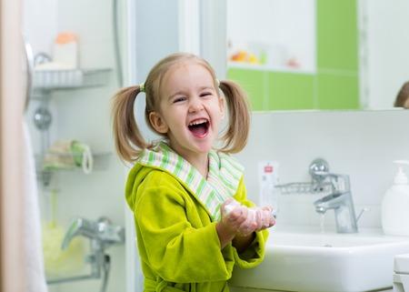 Smiling child little girl washing hands in bathroom